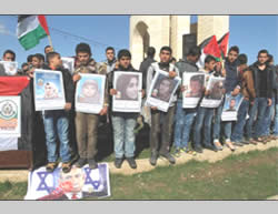 School children from Rafah identify with Palestinian terrorists killed during the current terrorist campaign. The two at the left stand on a picture of Israeli Prime Minister Benjamin Netanyahu (Facebook page of Safa News, December 6, 2015).