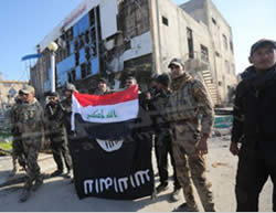 Iraqi soldiers waving the Iraqi flag and holding the ISIS flag upside down, as a symbol of ISIS's downfall in the city.