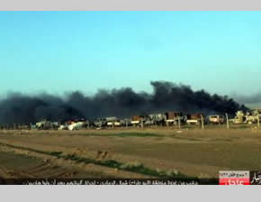 Iraqi Army vehicle in flames at a base north of the city of Ramadi, following an attack by ISIS