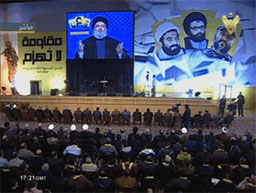 Hassan Nasrallah speaking at a memorial ceremony on the anniversary of the deaths of three senior Hezbollah operatives, pictured at the right. The Arabic at the left reads,