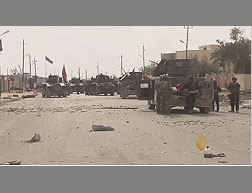 The Iraqi Army in the city of Hit. The ISIS flag can still be seen waving in the street (Al-Jazeera, April 10, 2016)