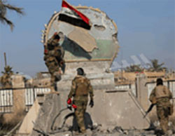 Iraqi soldiers fly the Iraqi flag near government buildings in the center of Ramadi, the capital of Anbar Province.