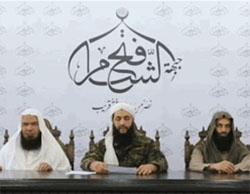 Al-Nusra Front leader Abu Mohammad al-Julani flanked by two officials from his organization, in an interview with Al-Jazeera TV in which he announces that the organization has been renamed the Fateh al-Sham Front (Al-Jazeera TV, July 28, 2016).  The insignia of the organization appears above, consisting of the name the Fateh al-Sham Front. In this interview with Al-Jazeera TV, Al-Julani appears unmasked for the first time.