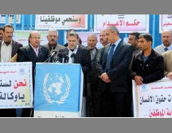 Dr. Suhail al-Hindi, chairman of the UNRWA staff union in the Gaza Strip, leads a demonstration of Gazan UNRWA workers to protest the agency's intention to reduce its budget for the Gaza Strip (Arab Today, August 2, 2015).