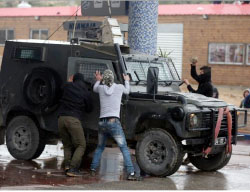 Palestinians attack an Israeli security vehicle with stones in the village of Nebi Saleh (Wafa, March 3, 2017).