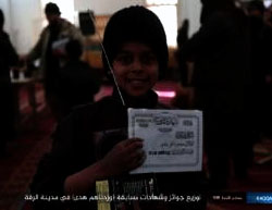 Boy who won a prize and a certificate of appreciation in a competition organized by ISIS in Al-Raqqah (Haqq, March 9, 2017)