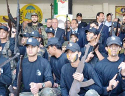 Children participating in the al-Futuwwa project at the Jamal Abd al-Nasser school in the eastern part of Gaza City photographed holding real and dummy rifles. In the background are senior figures from the Hamas administration's education and interior ministries in the Gaza Strip (Dunia al-Watan, April 4, 2013).
