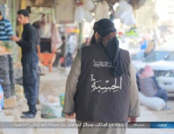 An operative of Al-Hisba (ISIS's morality police) observing an open market (Haqq, May 15, 2017).