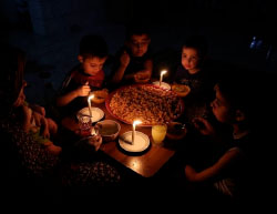 A family in the Gaza Strip breaks the Ramadan fast, eating by candlelight because of the lack of electricity (Facebook page of Shehab, June 12, 2017).