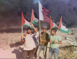 Demonstrators wave Palestinian and Qatari flags during a riot near the border security fence (Palinfo Twitter account, June 16, 2017).
