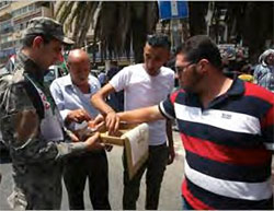 An operative of the PA security forces in Nablus hands out candy (Wafa, July 27, 2017).