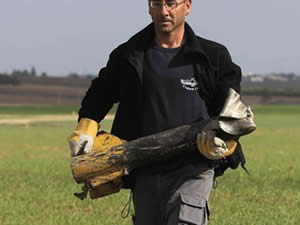 Israel police demolitions expert carries away the remains of a rocket fired during the latest round of escalation from the Gaza Strip