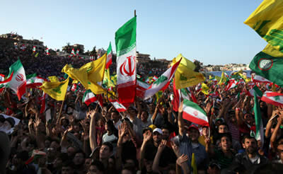 Supporters wave Hezbollah and Iranian flags to welcome Iranian President Ahmadinejad on his arrival in Lebanon