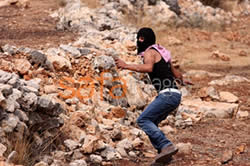 Masked Palestinian youth throws stones at IDF forces during the weekly demonstration at Bila�in