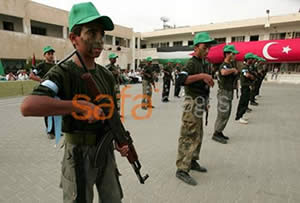 Children wearing green Hamas caps drilling with guns with the Turkish flag in the background