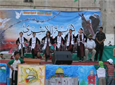 """Girls dance in front of a poster bearing the inscription """"Freedom for the prisoners"""""""
