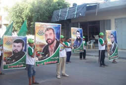 Children hold posters of Hamas terrorists imprisoned in Israel.