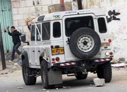 Protestor in Hebron throws rocks at an IDF vehicle
