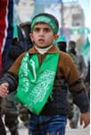 Child decorated with Izz al-Din al-Qassam Brigades banner and headband.