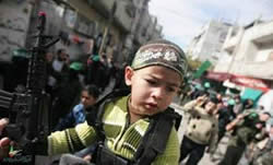Child carrying a weapon and wearing military equipment and a Hamas headband.