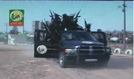 Armed Izz al-Din al-Qassam Brigades operatives standing on a police car