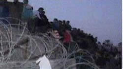 A Palestinian crowd gethering at the breach in the Rafah border fence