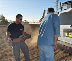 Israeli police demolitions expert removing a rocket from an open field