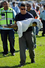 Police explosives expert carrying the remains of a rocket fired