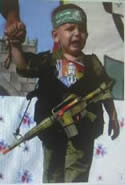 A preschool child in uniform and carrying a plastic rifle