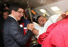 Turkish Foreign Minister Ahmet Davutoğlu greets one of the wounded operatives