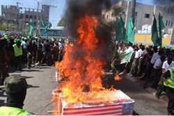 Coffins covered with the flags of Israel and the United States set on fire during a Hamas demonstration in central Gaza Strip refugee camps, organized as part of the wave of protest sparked by the film Innocence of Muslims