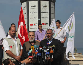 "Muhammad Kaya (center) holds a press conference at the monument erected by Hamas for the ""activists"" killed aboard the Mavi Marmara (Alresala.net website, November 4, 2012)."