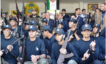 Al-Futuwwa students at the Gamal Abdel Nasser in eastern Gaza City. They are holding both real and dummy rifles. In the background are senior members of the education and interior ministries of the de-facto Hamas administration, responsible for the program (Dunia Al-Watan, April 4, 2013).
