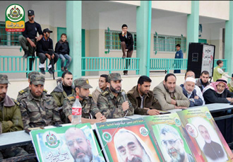 "Lieutenant Colonel Mahmoud al-Nahale, in charge of Al-Futuwwa for the Hamas ministry of the interior (center, holding microphone), with Al-Futuwwa instructors and others involved in the program. They are at a ceremony to mark ""Palestinian prisoner day"" and the anniversary of the death of Hamas leader Abd al-Aziz Rantisi. The ceremony was held at a school in the town of Qarara, northeast of Khan Yunis in the southern Gaza Strip. The pictures hung below the stage are of Hamas figures, including Sheikh Ahmed Yassin and Abd al-Aziz Rantisi  (Al-Futuwwa Facebook page, April 20 26, 2013)"