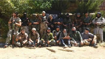 Foreign fighters from the Caucasus (mainly Chechens) in Syria against a background of Al-Qaeda flags (http://fisyria.com, August 3, 2013).