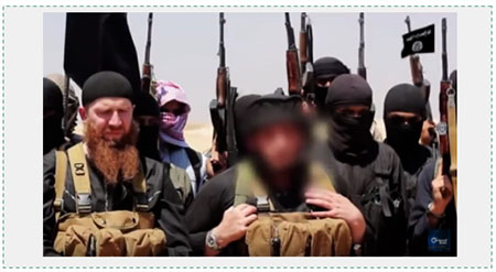 Abu Mohammad al-Adnani (in the middle, with his face blurred) alongside Omar the Chechen (on the left). The two men appear in the video released by ISIS when the establishment of the Caliphate was announced (YouTube, June 29, 2014)