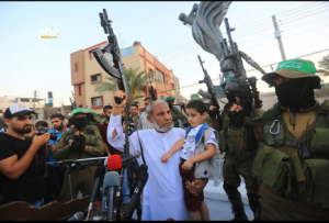 During the ceremony senior Hamas figure Mahmoud al-Zahar raises a rifle with one hand and holds Mazen Fuqahaa's son with the other (Facebook page of QudsN, August 7, 2017).