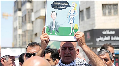 Khaled Mansour, member of the political bureau of the Palestinian People's Party at the demonstration, waving a caricature depicting Jared Kushner as Israel's pet (Asharq Al-Awsat, 25 August 2017)