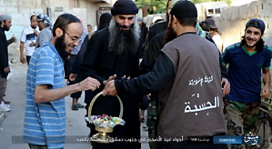 An ISIS Islamic Police man (Al-Khasba) handing out sweets to the locals (Akhbar Al-Muslimeen, 2 September 2017).