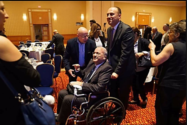 Saeb Erekat in a wheelchair pushed by Husam Zomlot, the PA representative to the United States, at a conference of the Arab and Palestinian dispersal in America.