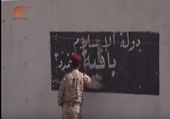 "An Iraqi soldier wipes out the slogan reading, ""the Islamic State stands firm and is spreading,"" written on a wall in 'Anah (al-Mayadeen, September 25, 2017)."
