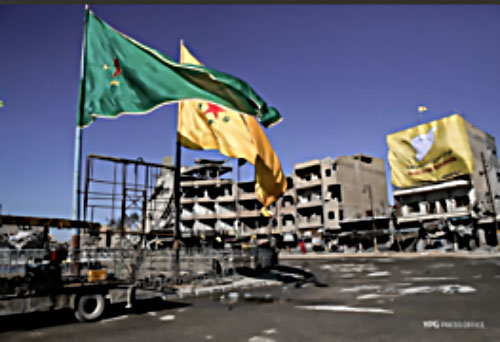 Al-Naim Square in Al-Raqqah. Right: A giant flag of the SDF forces hanging on a building façade. Left: Giant flags of Kurdish organizations in Syria (YPG and YPJ) which are the predominant factor of the SDF forces (Twitter account, October 18, 2017)