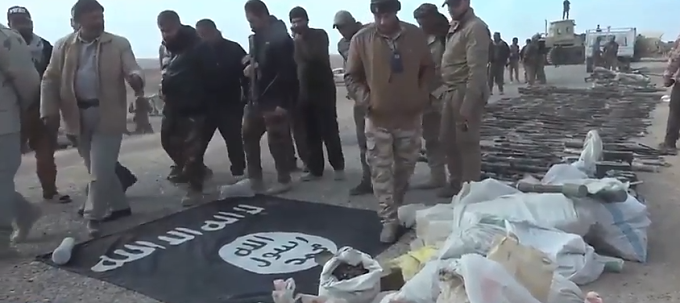 ISIS weapons and flag found by the Al-Abbas Division east of Jineef airfield (YouTube account of the Iraqi Military Spokesman's Office, November 26, 2017)