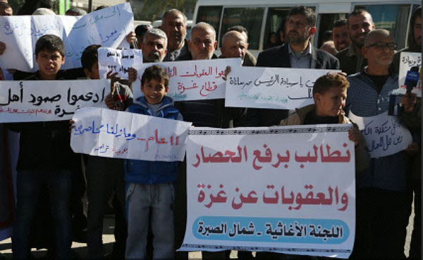 Gazans demonstrate in front of the government's offices demanding the sanctions imposed on the Gaza Strip be lifted immediately (Palinfo Twitter account, December 4, 2017).