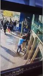 Security camera photograph of a Palestinian terrorist stabbing an Israeli security guard at the entrance to the central bus station in Jerusalem.