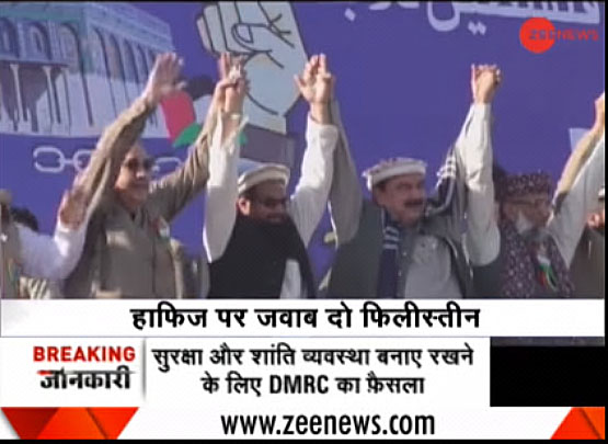 Palestinian ambassador Walid Abu Ali (left) holds hands with Hafiz Muhammad Saeed (center) at the rally (Indian Zee News YouTube TV channel, December 29, 2017).