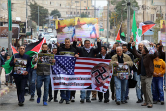 March in Bethlehem held to protest the Trump declaration. Marchers carry an American flag with a picture of Trump covered by a swastika and the inscriptions,