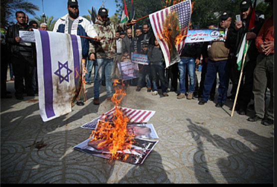 Burning the American and Israeli flags and a picture of Donald Trump at a rally in Gaza (Twitter account of Palinfo, December 31, 2017).