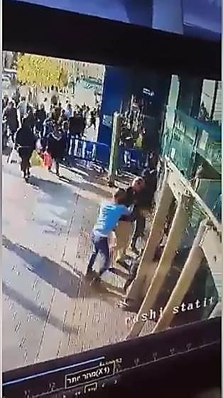 A Palestinian stabs an Israeli security guard at the entrance to the central bus station in Jerusalem (picture from a security camera video). (Facebook page of QudsN, December 10, 2017).