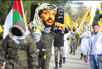 "Signs held at the march: at the right is a picture of Yusuf al-Shaib, the Fatah coordinator of student activities at Bir Zeit University, detained by the IDF on December 16, 2017. At the left is a picture of Yasser Arafat; the Arabic reads ""A million shaheeds are marching to Jerusalem"" (Facebook page of the Fatah student movement at Bir Zeit University, January 3, 2018)."